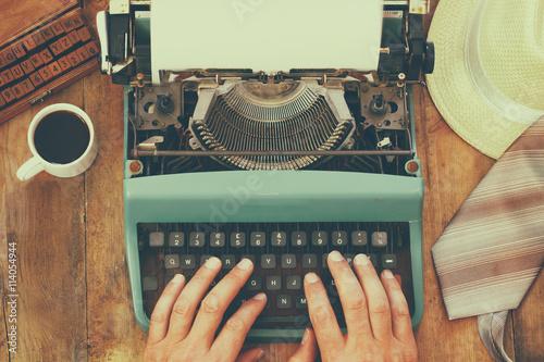 Keuken foto achterwand Retro man typing on vintage typewriter with blank page