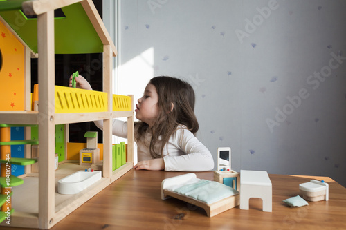 Valokuvatapetti A little girl playing with her dollhouse