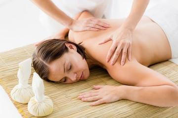 Obraz na płótnie Canvas Naked woman receiving massage from masseur