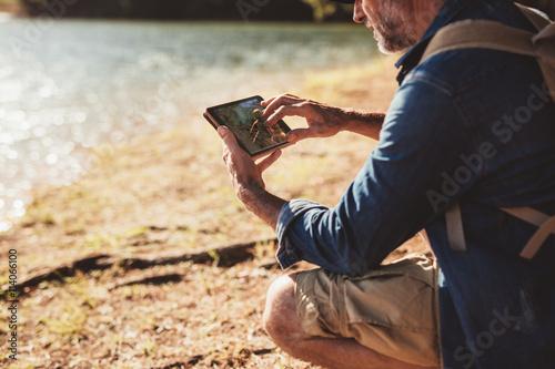 Fotografia  Dojrzały człowiek na wycieczce za pomocą zakładki do nawigacji