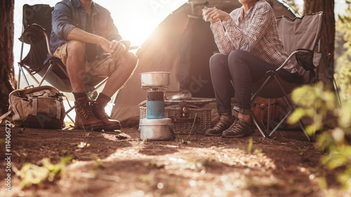 Photo sur Aluminium Camping Couple sitting in chairs outside the tent