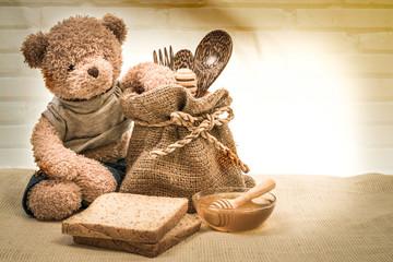 Fototapetacup honey on sackcloth with Teddy
