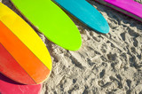 Fototapeta Tęcza - Gay pride rainbow color stand up paddle long board surfboards rest together on the beach in Rio de Janeiro, Brazil