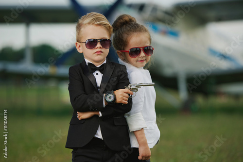 young boy and girl playing spy плакат