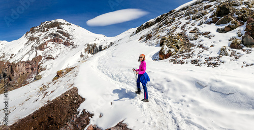 obraz PCV woman hiking on a snowy trail in the Caucasus mountains on the background of unusual lenticular cloud