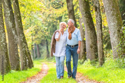 Obraz Älteres Paar macht Spaziergang im Wald - fototapety do salonu