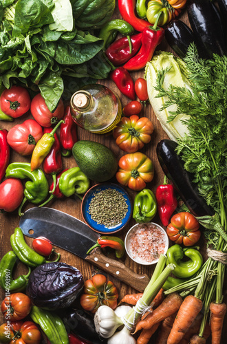 Poster Cuisine Fresh raw vegetable ingredients for healthy cooking or salad making, top view. Olive oil in bottle, spices and knife
