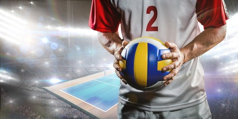 Fototapeta Composite image of sportsman holding a volleyball