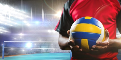 Fototapeta Sport Composite image of mid-section of sportsman holding a volleyball