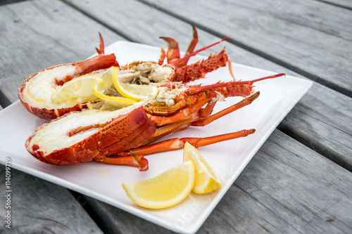 Poster Coquillage Cooked and halved New zealand crayfish on the wooden table.