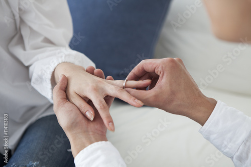Fotografia The man is wearing an engagement ring on the left ring finger of the woman