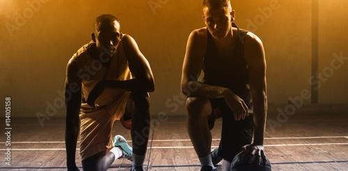 Plakat Portretów gracze koszykówki pozuje na ich kolanach