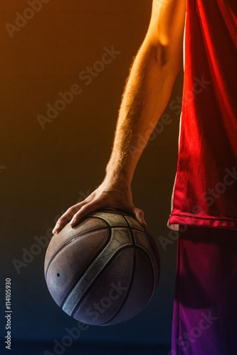 Close up on basketball held by basketball player Fotobehang