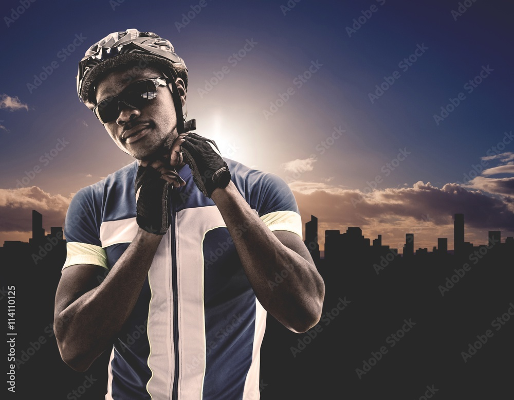 Fotografie, Tablou  Composite image of athletic man putting his cycling helmet