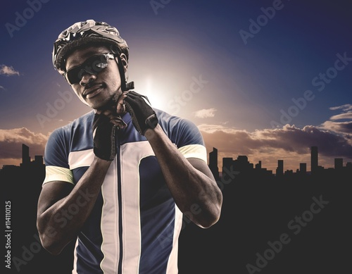 Plakat Composite image of athletic man putting his cycling helmet