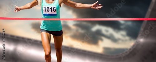 Fotografía Composite image of sportswoman finishing her run