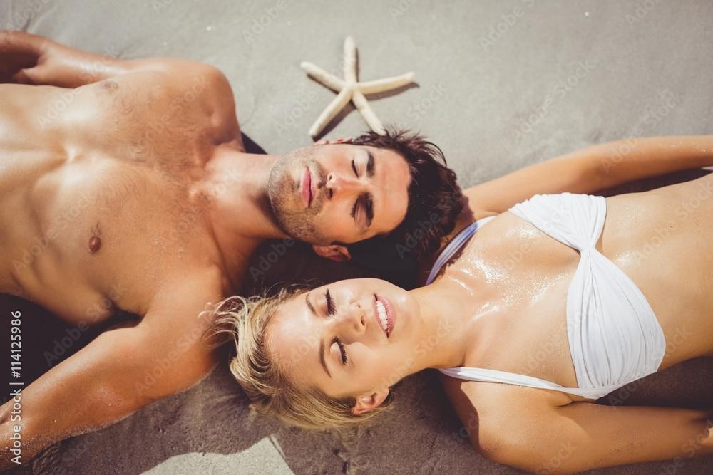 Fototapety, obrazy: Couple lying on beach