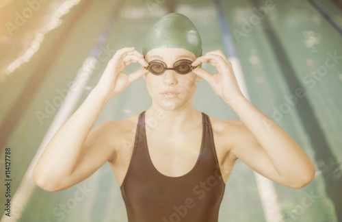 Woman in swimsuit adjusting her goggles Canvas Print
