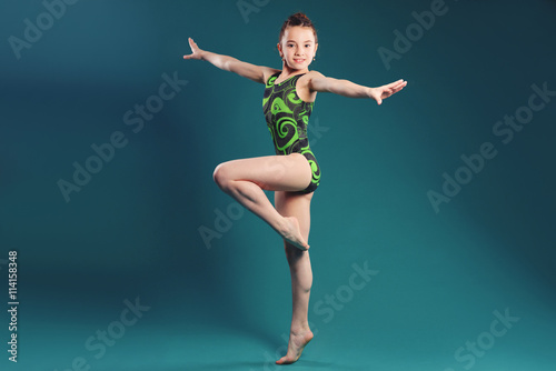 Photo Stands Gymnastics little girl acrobat. exercises. fitness