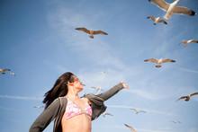 Young Woman Reaching Towards Gulls