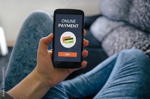 Fotografía  Muchacha que sostiene teléfono inteligente con el concepto de pago en línea en la pantalla