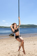 curly brunette on sea beach with pole