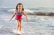 Little girl playing in the waves at sea on a sunny day.