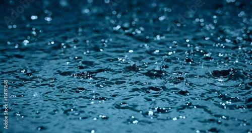 Fotografiet heavy rain water drops on surface street