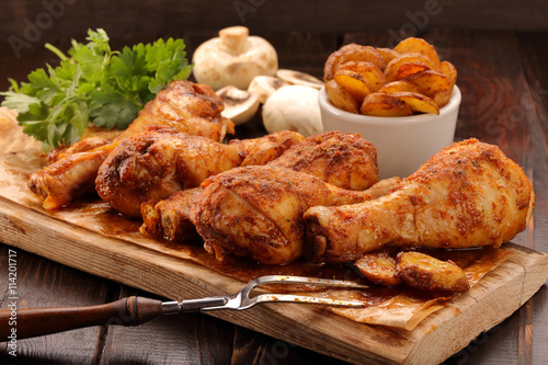 plakat Roasted chicken legs with potato chips and vegetables