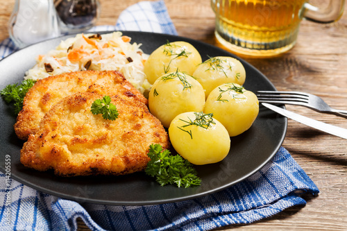 plakat Fried pork chop in breadcrumbs, served with boiled potatoes and