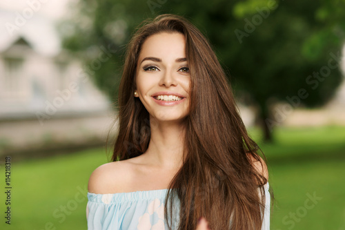 Fototapety, obrazy: Young beautiful woman with long brunette hair and perfect smile. Happy girl posing in park and looking in camera