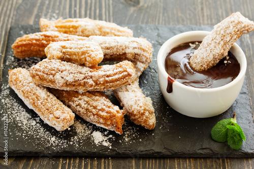 Churros with hot chocolate and powdered sugar.
