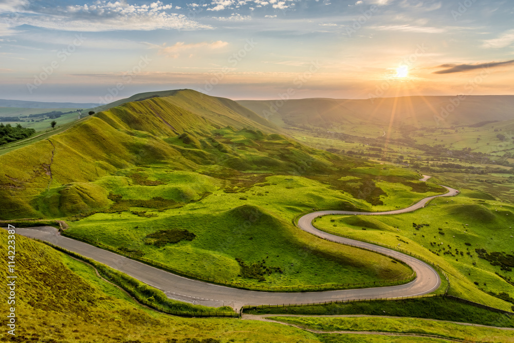 Fototapety, obrazy: Long winding country road leading through rural countryside in the English Peak District with beautiful evening sunlight.