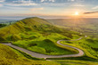 canvas print picture - Long winding country road leading through rural countryside in the English Peak District with beautiful evening sunlight.