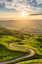 Winding Country Road Leading To Edale In The English Peak District With Beautiful Golden Light Shining Through Valley.