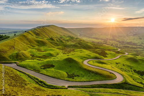 Foto op Plexiglas Beige Long winding country road leading through rural countryside in the English Peak District with beautiful evening sunlight.