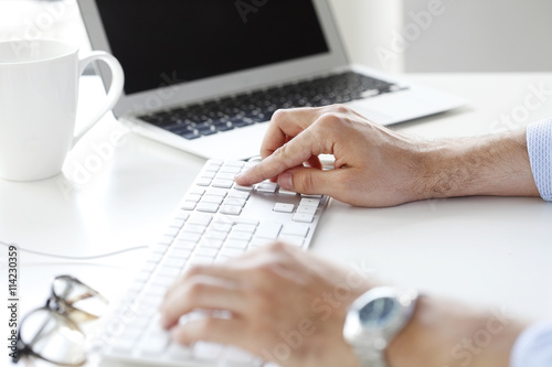 Typing on keyboard. Close-up image of hands working on a computer keyboard.