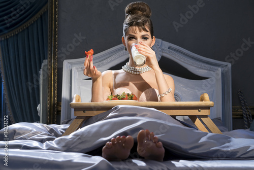 Photo  Girl like a movie star  in bed breakfast - drinking milk and eating strawberries