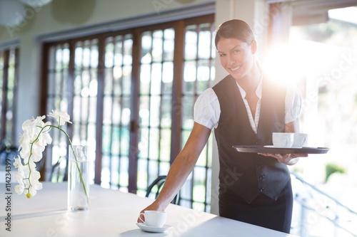Fotografía  Smiling waitress serving cup of coffee