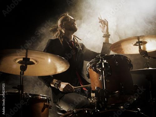 Fotografia Silhouette drummer on stage. Dark background, smoke spotlights