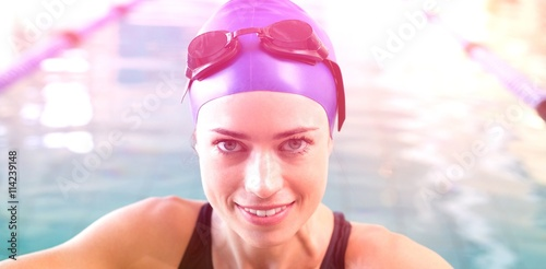 Fit swimmer in the pool smiling at camera Poster