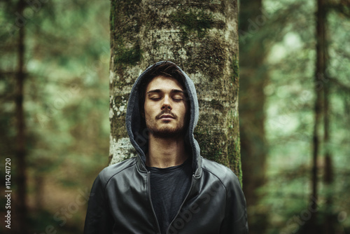Fotografía  Man leaning on a tree with eyes closed