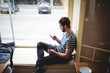 Side view of man using cellphone at cafe
