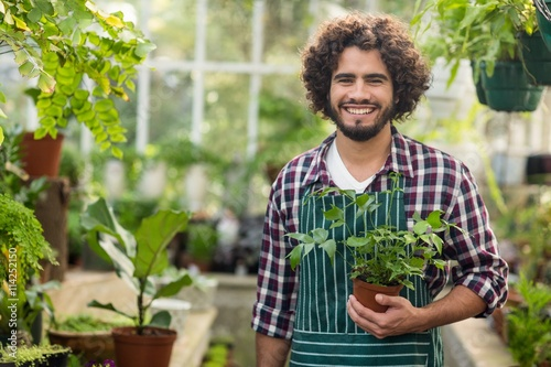 Photo Smiling male gardener holding potted plant