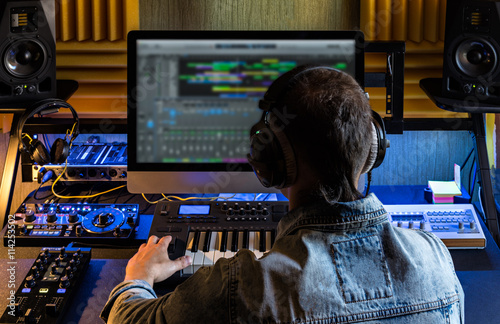 Photo  One man produce electronic music in project home studio.