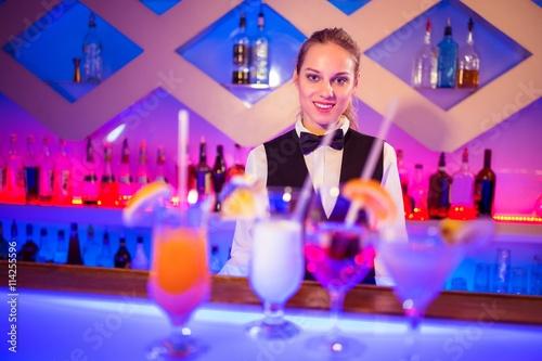 Photo Pretty barmaid standing at bar counter