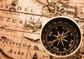 antique compass on vintage map background