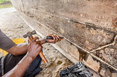 Keuken foto achterwand Schip Man repairing a fishing old boat in Kenya, Africa
