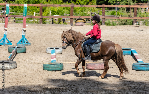 Poster Equitation little girl is riding a horse