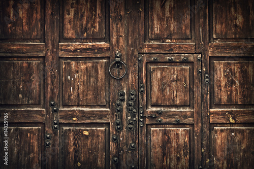 background old wooden gate with metal handle and rivets